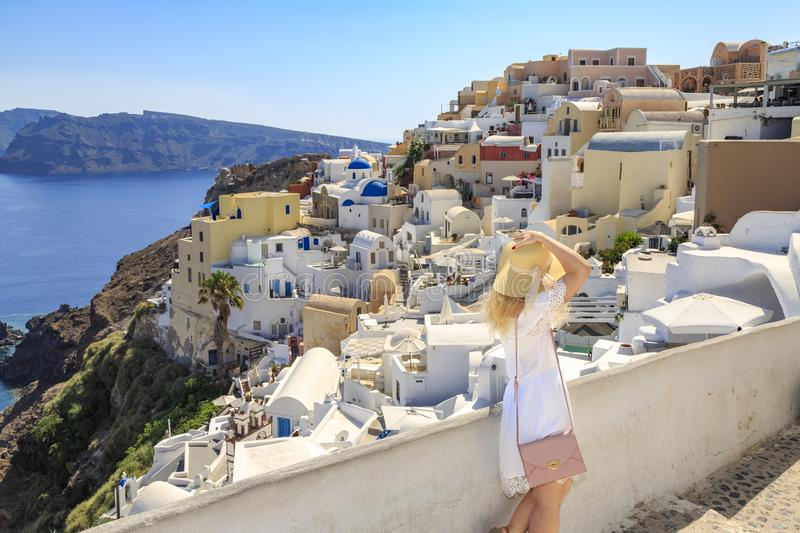 Blonde woman looking at cityscape of Oia village in Santorini island. Greece stock photo