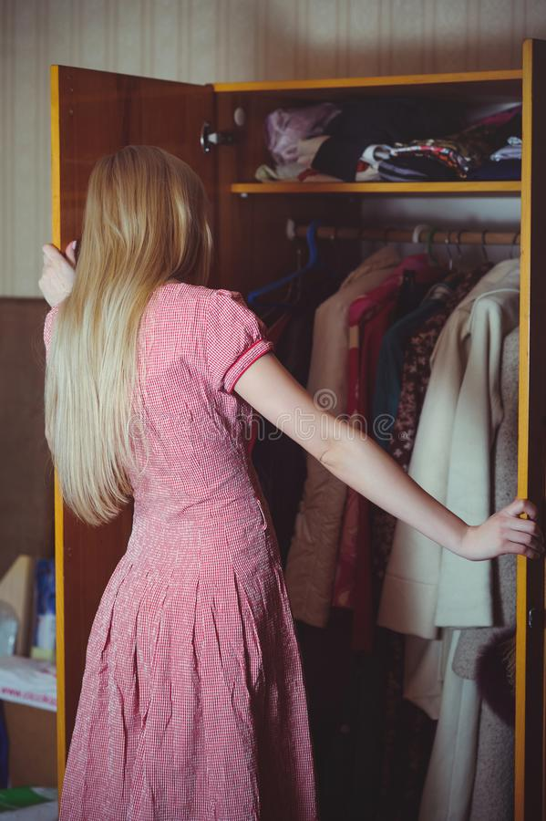 Blonde woman looks in a closet, dressed in a red dress, stands in an old house, a simple home image.  royalty free stock photo