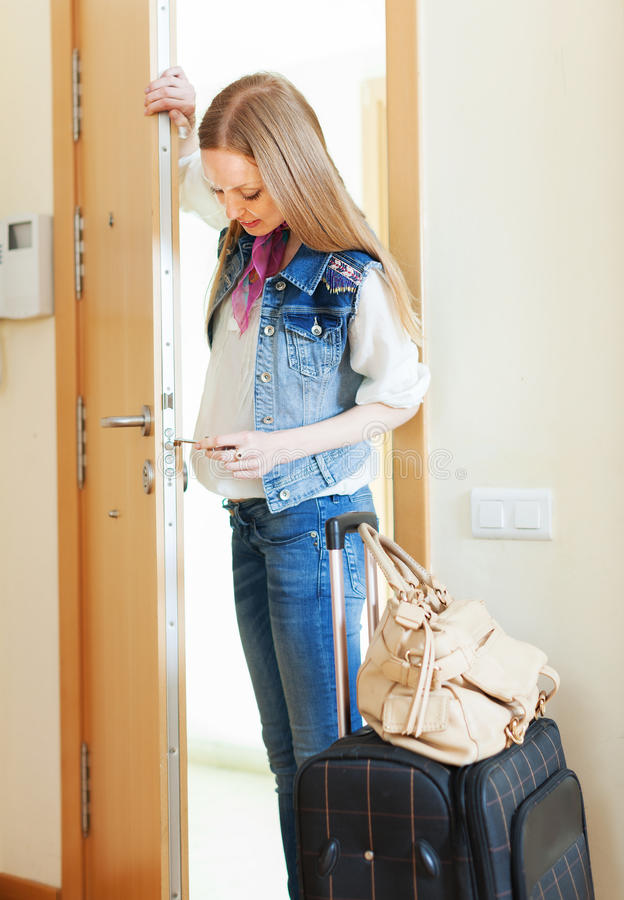 Blonde woman with luggage loocking door lock royalty free stock images