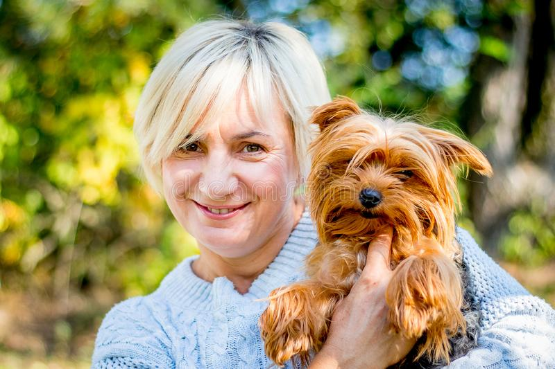 Blonde woman with a magic smile holds a small dog in her arms_ royalty free stock photography