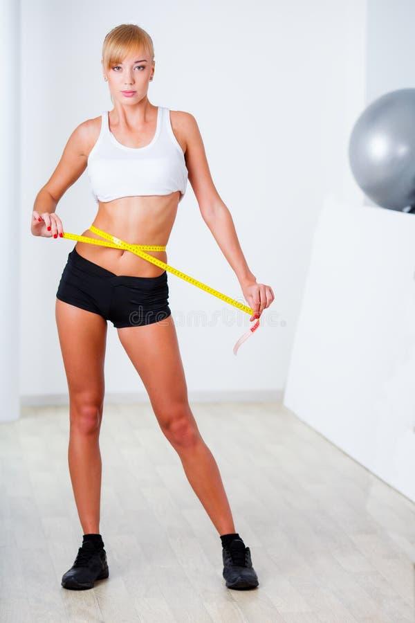Blonde woman measuring her waistline stock image