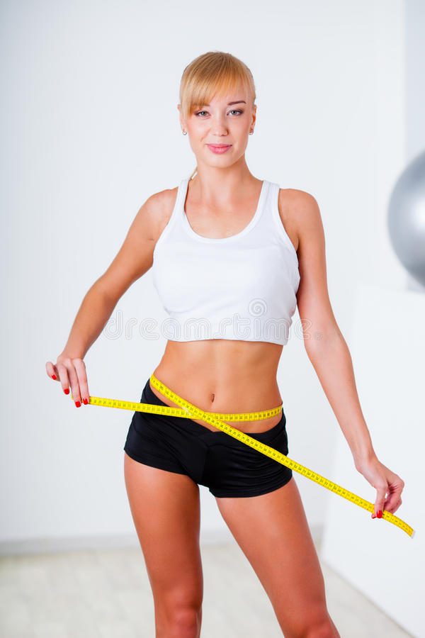 Blonde woman measuring her waistline. With yellow tape stock photo