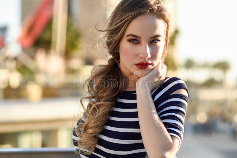 Blonde woman, model of fashion, sitting in urban background. royalty free stock photos