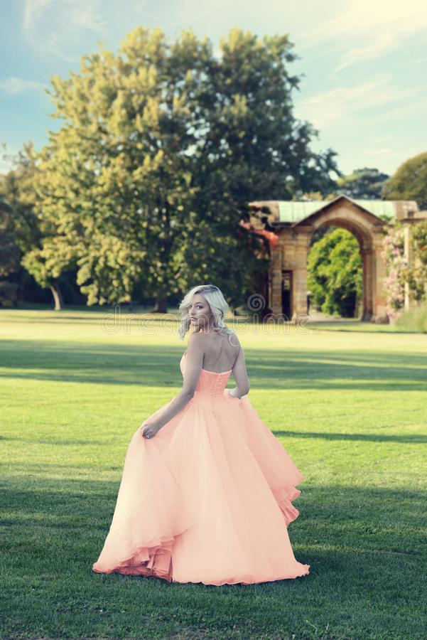 Blonde woman in peach color tulle ball dress walking in formal garden stock photos