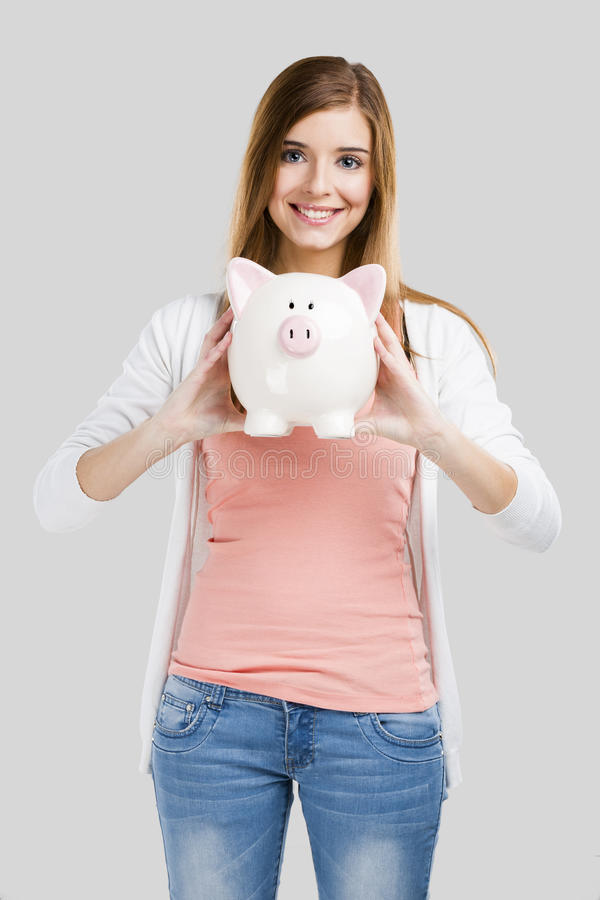 Blonde woman with a piggy bank stock image