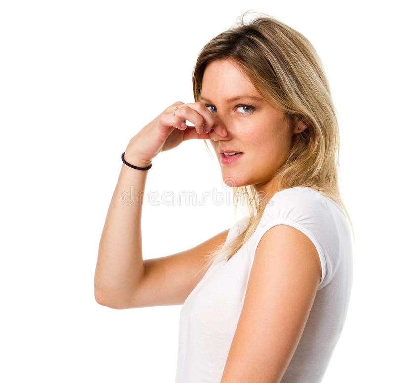 Blonde woman pinching her nose. Woman experiencing a bad smell, pinching her nose stock photo