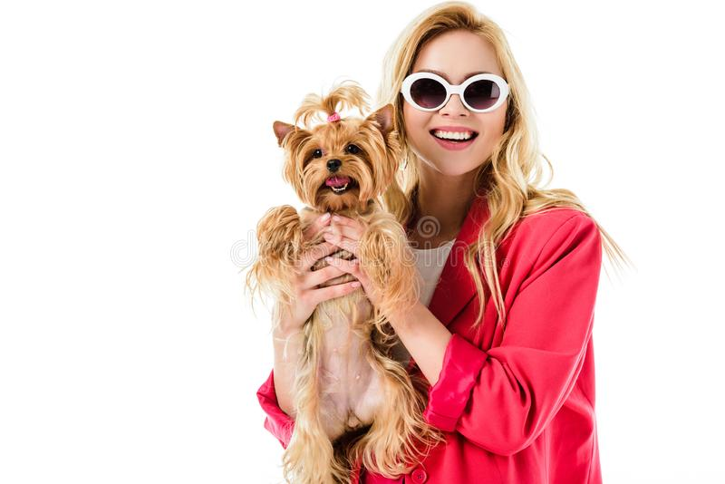 Blonde woman in pink clothes holding cute dog stock image