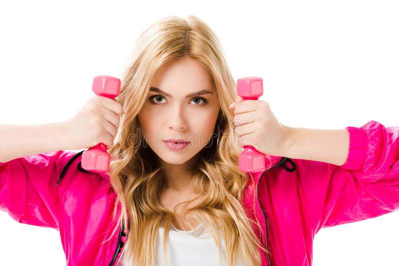 Blonde woman in pink clothes holding dumbbells royalty free stock photography