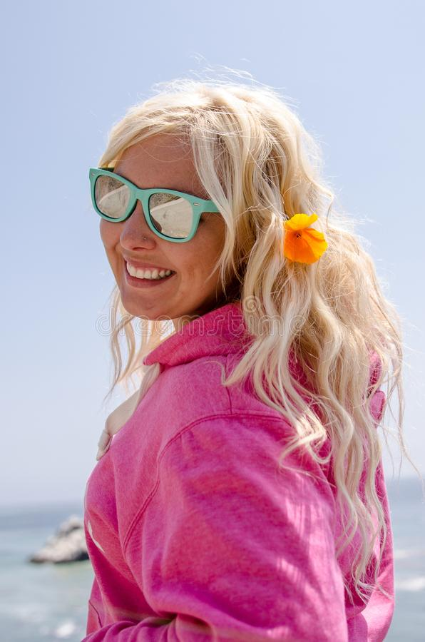 Blonde woman poses along the California Pacific Coast Highway with a poppy in her blonde hair. Blonde woman poses along the California Pacific Coast Highway with stock image
