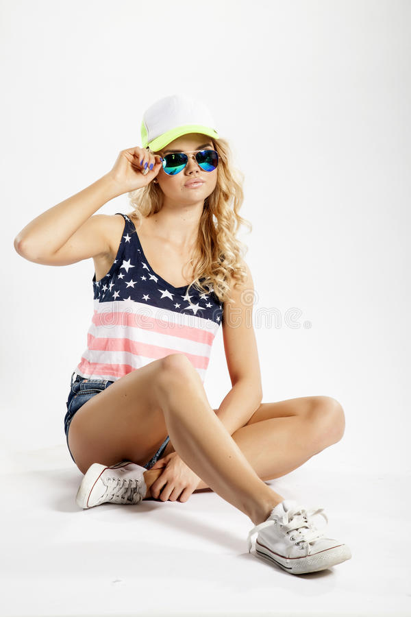 Blonde woman posing in American flag shirt. Portrait of a pretty blonde young adult beauty woman posing in American flag shirt and baseball cap isolated on white stock photos