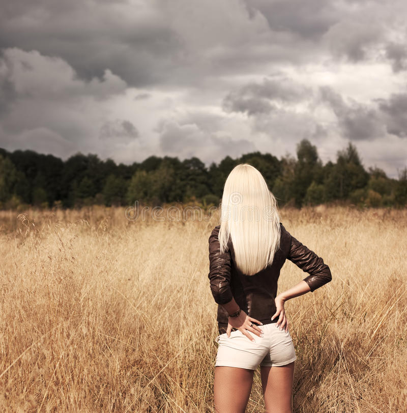 Blonde Woman Posing at the Field. Rear View royalty free stock photography