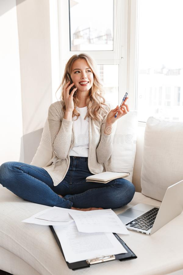 Blonde woman posing sitting indoors at home using laptop computer talking by mobile phone royalty free stock images