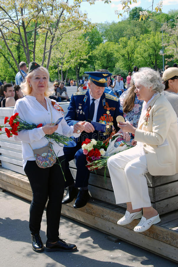 A blonde woman present flowers to war veterans. MOSCOW - MAY 09, 2016: A blonde woman present flowers to war veterans. Victory Day celebration in Gorky park in royalty free stock photos