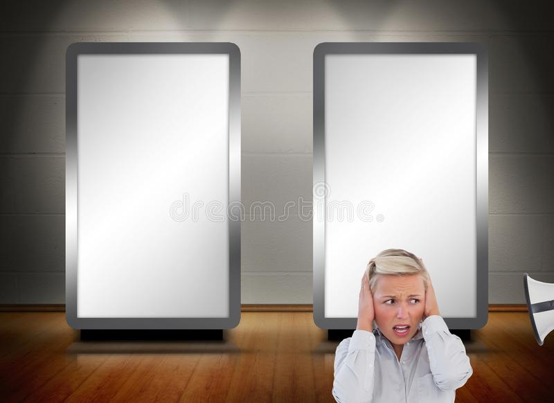 Blonde woman protecting her ears from bullhorn. Composite image of blonde women protecting her ears from bullhorn in front of two white screens stock photo