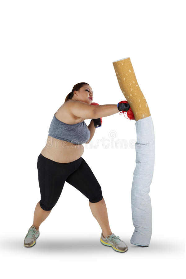 Blonde woman punching a cigarette. Image of blonde hair woman wearing sportswear while punching a cigarette, isolated on white background stock images