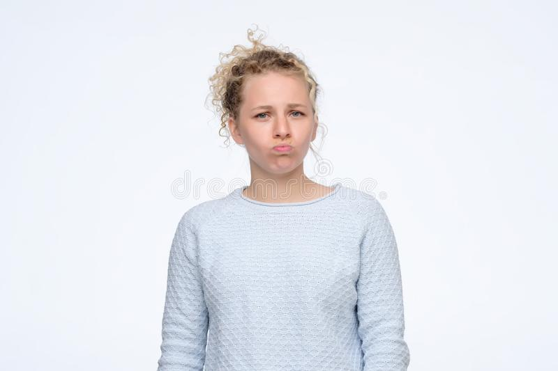 Blonde woman with pursed lips looking at camera being offended. Thoughtful blonde woman with pursed lips looking at camera being offended. Studio shot stock photo
