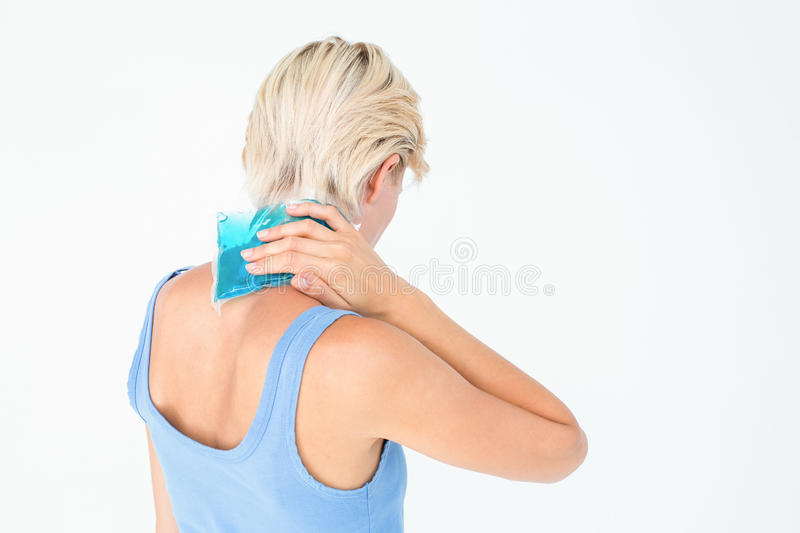 Blonde woman putting gel pack on neck stock photos