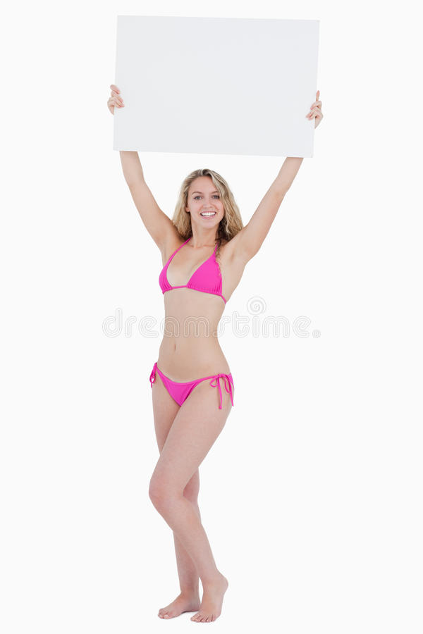 Blonde woman raising a blank poster above her head
