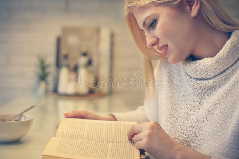 Blonde woman reading a book. royalty free stock image