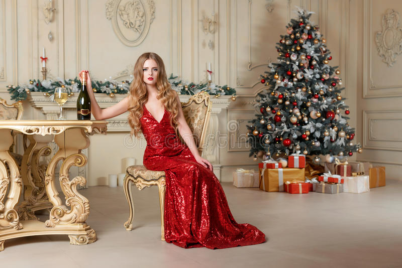 Blonde woman in red dress with glass of white wine or champagne siting on a chair in luxury interior. Christmas tree stock image