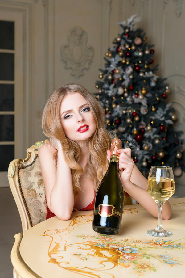 Blonde woman in red dress with glass of white wine or champagne siting on a chair in luxury interior. Christmas tree, presents and stock photos