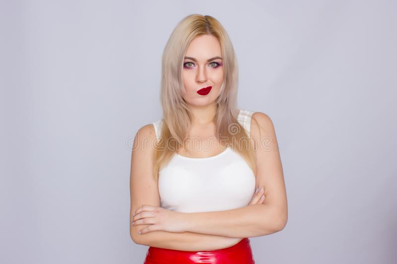 Blonde woman in red leather skirt and white shirt. Fashionable young blonde woman posing wearing red leather skirt and white shirt , looking to camera royalty free stock photo