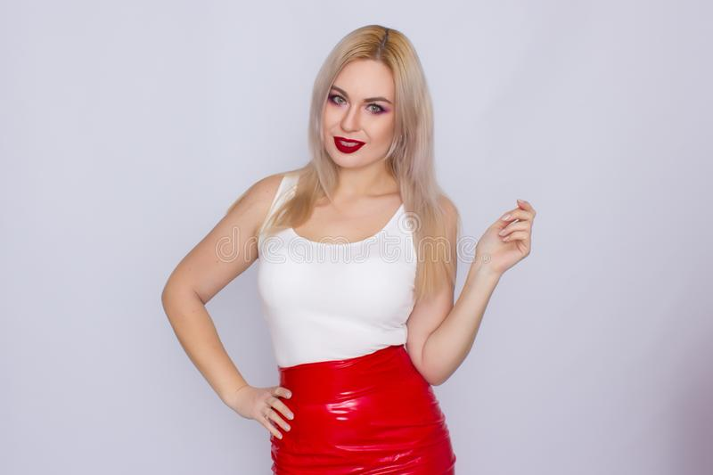 Blonde woman in red leather skirt and white shirt. Fashionable young blonde woman posing wearing red leather skirt and white shirt , looking to camera royalty free stock photos