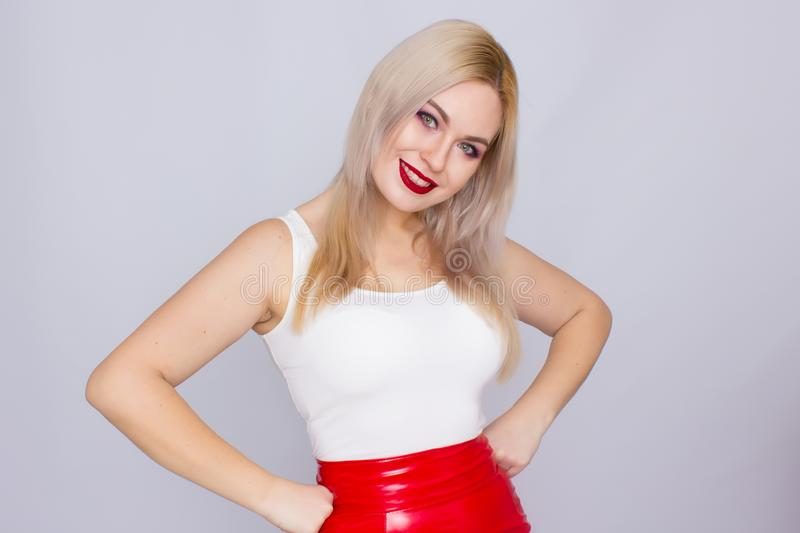 Blonde woman in red leather skirt and white shirt. Fashionable young blonde woman posing wearing red leather skirt and white shirt , looking to camera royalty free stock photography