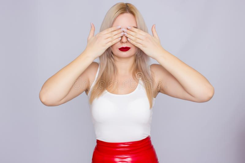 Blonde woman in red leather skirt and white shirt. Fashionable young blonde woman posing wearing red leather skirt and white shirt , looking to camera stock photo