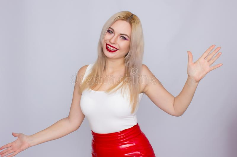 Blonde woman in red leather skirt and white shirt. Fashionable young blonde woman posing wearing red leather skirt and white shirt , looking to camera royalty free stock images