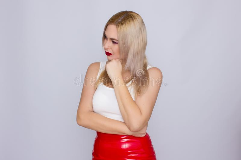 Blonde woman in red leather skirt and white shirt. Fashionable young blonde woman posing wearing red leather skirt and white shirt , looking to camera stock photography