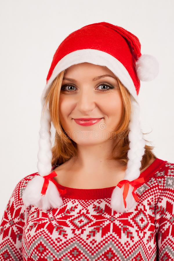 Blonde woman in red New Year`s sweater and New Year`s cap on white background royalty free stock images