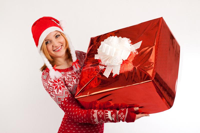 Blonde woman in red New Year`s sweater and New Year`s cap on white background holds big present stock images