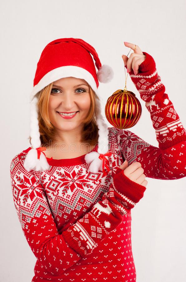 Blonde woman in red New Year`s sweater and New Year`s cap on white background holds Christmas tree ball stock photo