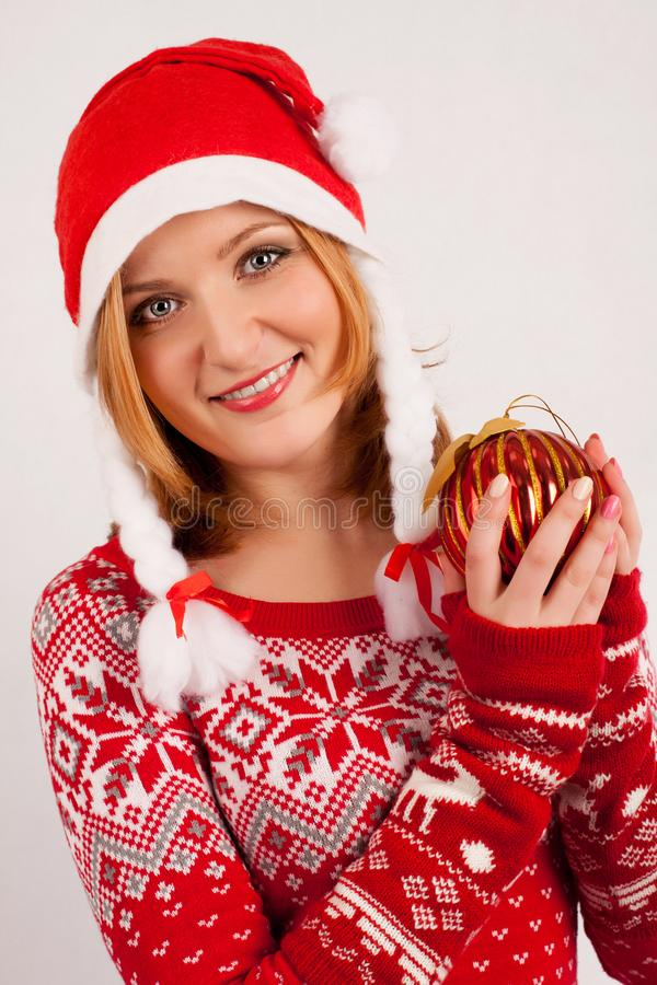 Blonde woman in red New Year`s sweater and New Year`s cap on white background holds Christmas tree ball royalty free stock images