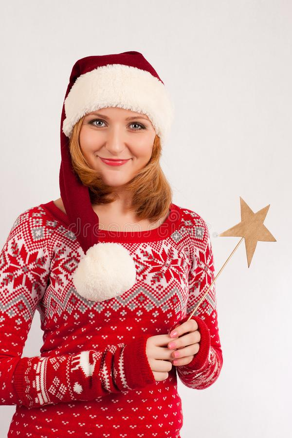 Blonde woman in red New Year`s sweater and New Year`s cap on white background holds magic wand with star royalty free stock photo