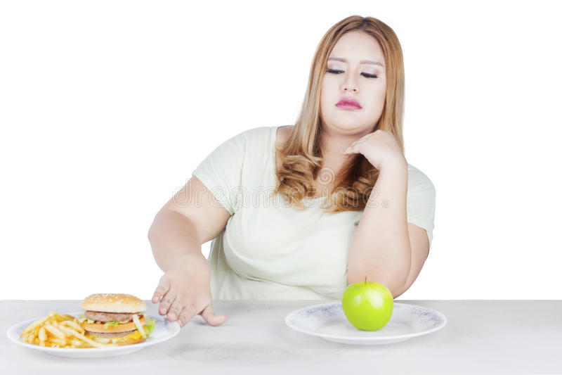 Blonde woman refuses hamburger. Photo of a blonde woman with overweight body refusing a plate of hamburger on the table royalty free stock photography