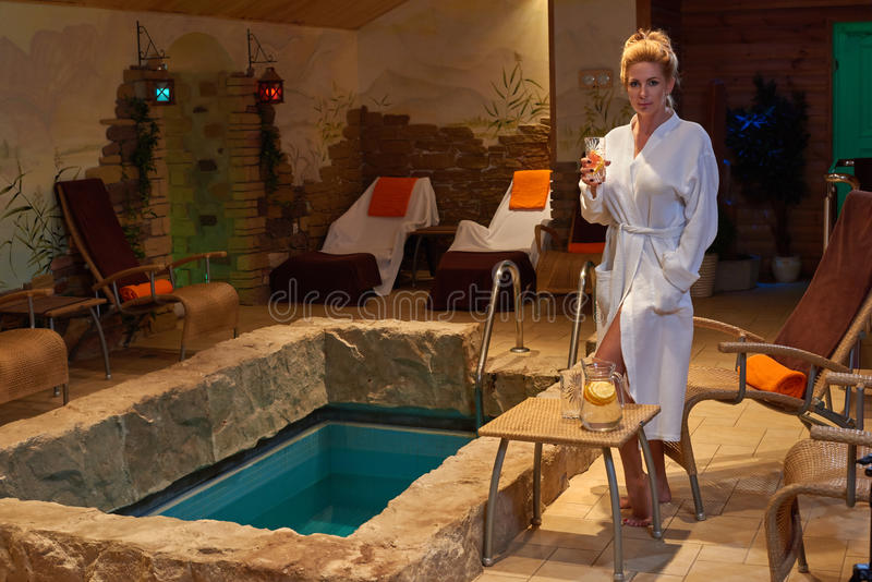 Blonde woman relaxing at indoor pool royalty free stock photography