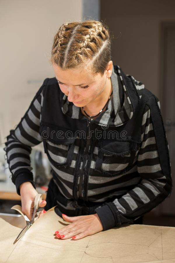 Blonde woman seamstress cuts from craft paper pattern for making clothes.  royalty free stock images