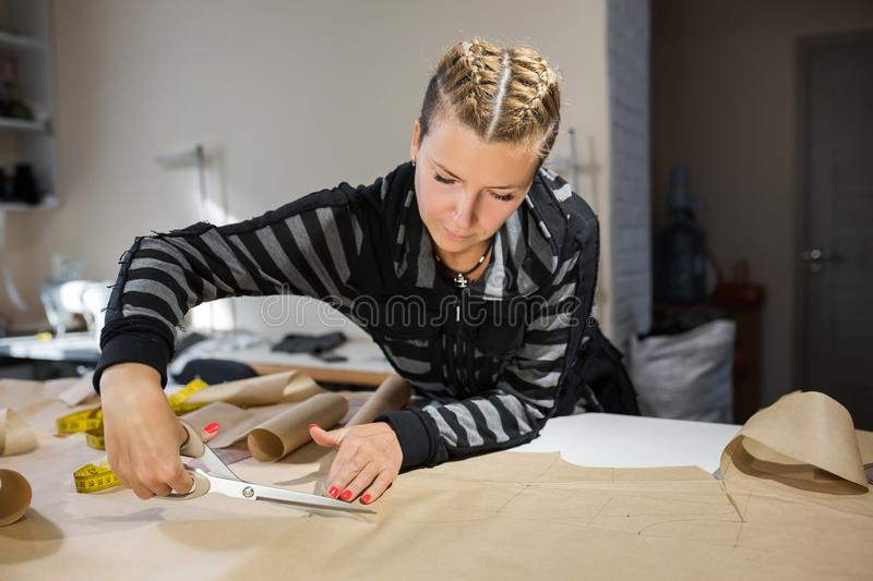 Blonde woman seamstress cuts from craft paper pattern for making clothes.  royalty free stock photos