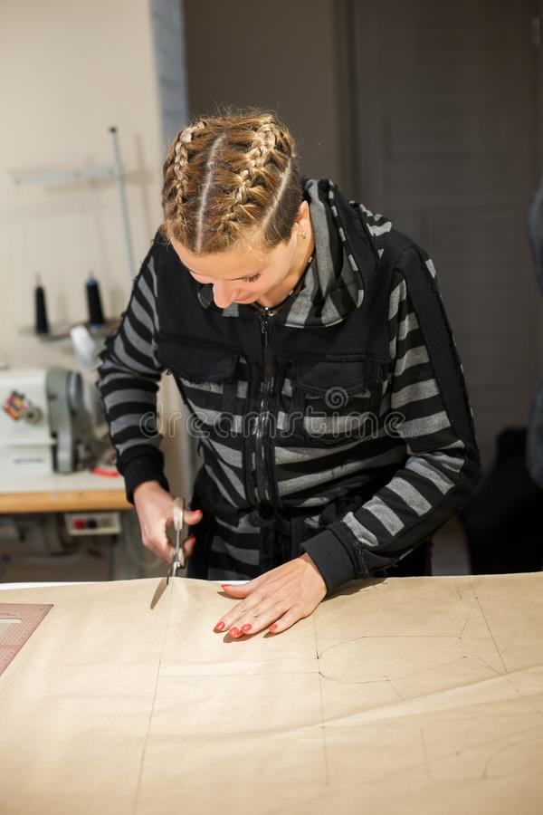 Blonde woman seamstress cuts from craft paper pattern for making clothes.  stock images