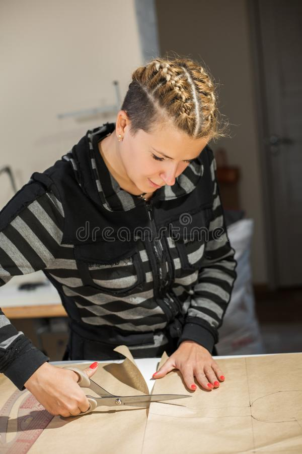 Blonde woman seamstress cuts from craft paper pattern for making clothes.  stock photography