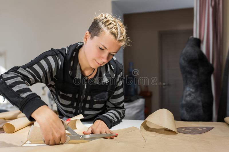 Blonde woman seamstress cuts from craft paper pattern for making clothes.  stock photos