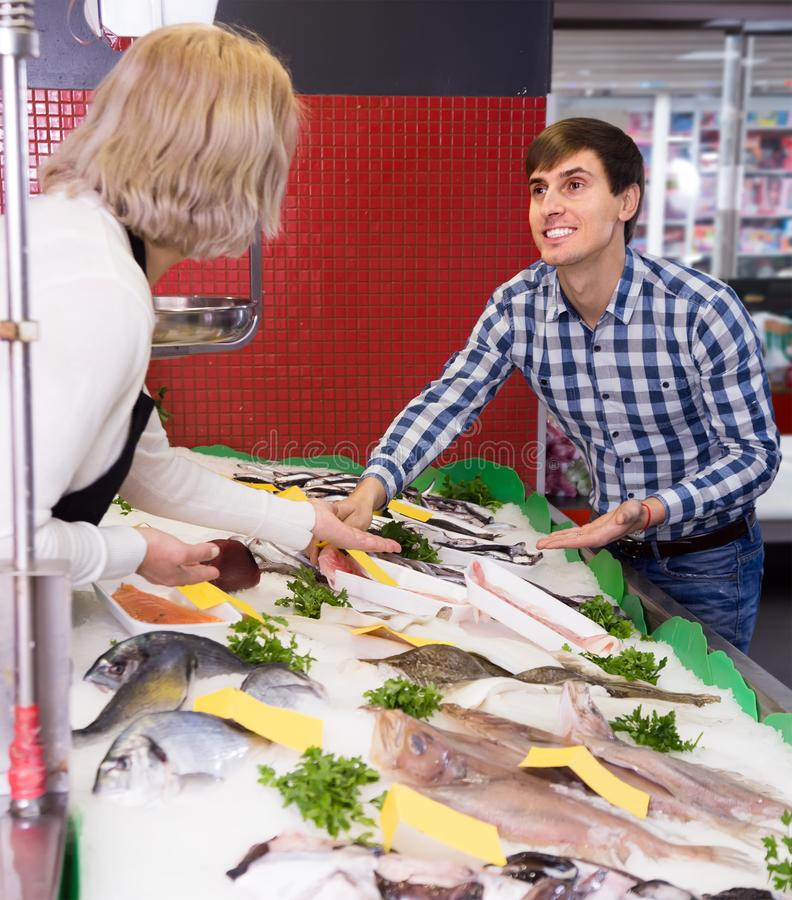 Blonde woman selling fish to male customer in store. Mature blonde women selling fish to male customer in store royalty free stock photo