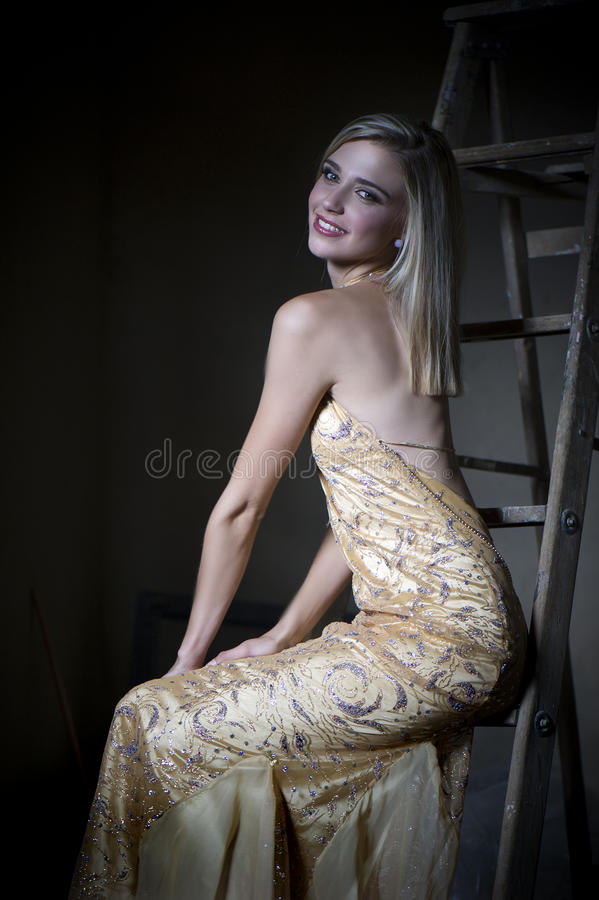 Blonde woman in golden evening dress. Color image of a beautiful young blonde woman wearing a revealing and golden couture evening dress, seated on a ladder in stock image