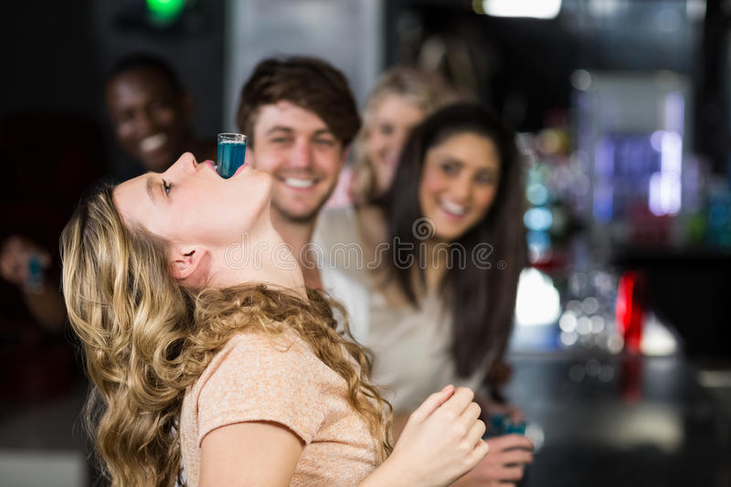 Blonde woman with a shot in her mouth royalty free stock photos