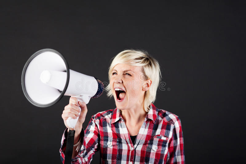 Blonde Woman Shouting Into Megaphone. Young blond woman shouting into the megaphone against black background royalty free stock photo