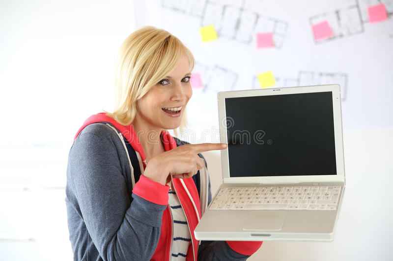 Blonde woman showing text on laptop. Young woman pointing at laptop screen stock image