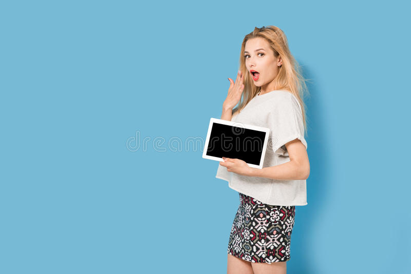 Blonde woman shows her tablet pc stock photography