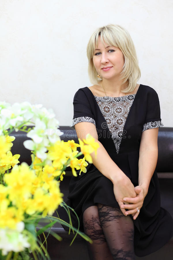 Blonde Woman Sits On Black Leather Couch Stock Image